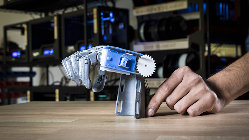 The University of Washington team 3D printed an e-NABLE arm with a prototype of their bidirectional sensor (blue and white) that monitors the hand opening and closing by determining the angle of the wrist (Credit: Mark Stone/ University of Washington)