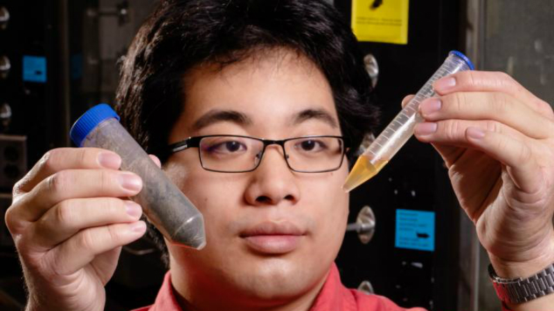 Mechanical science and engineering graduate student Timothy Lee holds a sample of waste and a sample of distillate the team derived from that waste (Credit: L. Brian Stauffer)