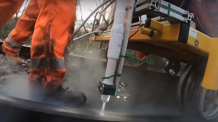 The supersonic dry ice stream blasts the track during tests of the technology tackling 'leaves on the line' (Credit: University of Sheffield)