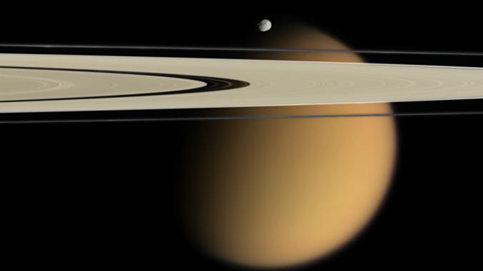 (Cassini's image showing tiny moon Epimetheus and Titan, behind, with Saturn's A and F rings stretching across the picture. Credit: NASA)